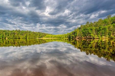 Photo Of Haliburton Lake With Calm Water, Green Shoreline, Overcast Sky