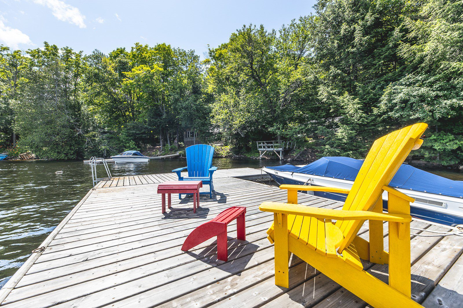 Yellow and Red muskoka chais sitting on the dock of 1023 Rolland Drive.