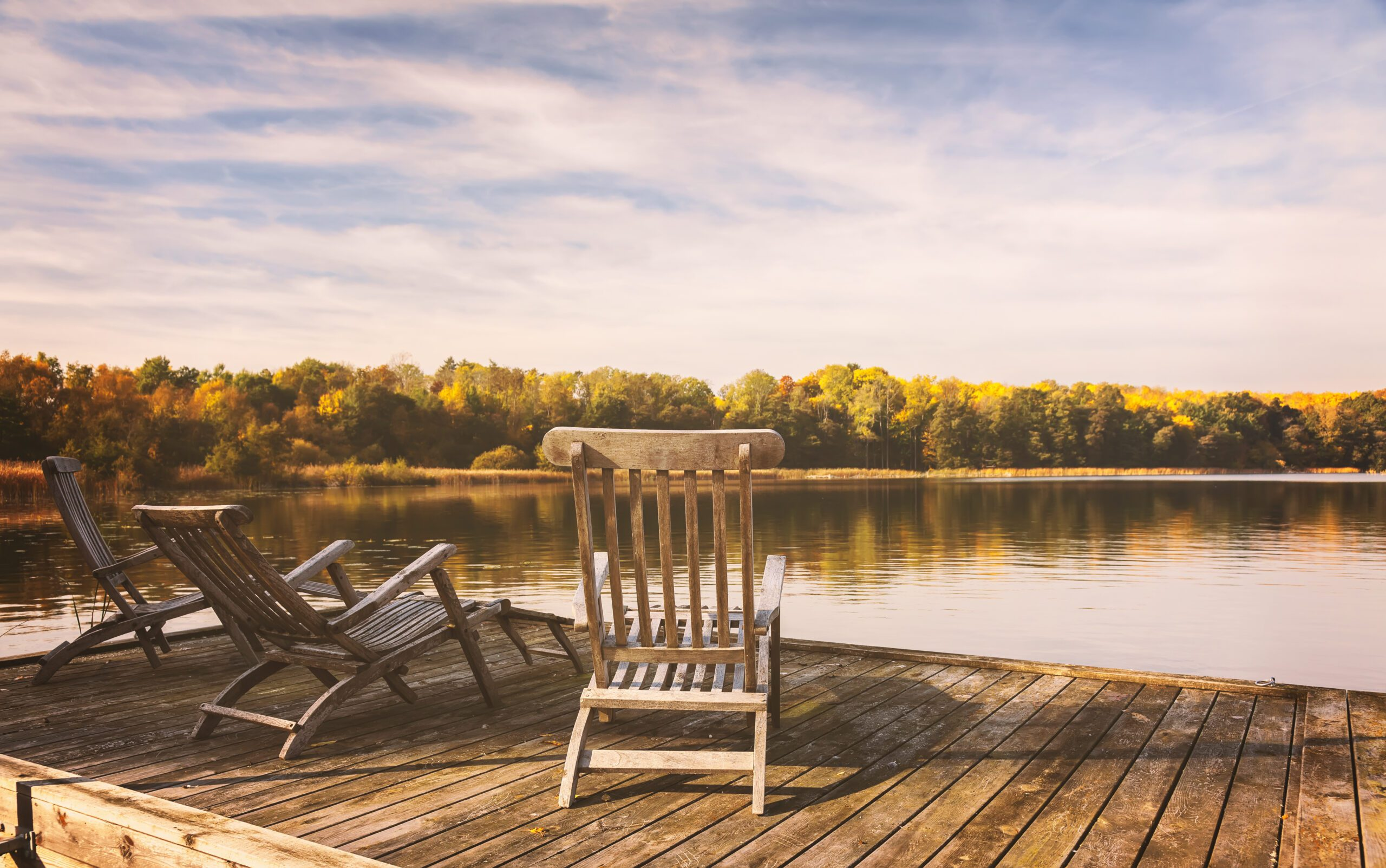 Two Chairs On A Dock Overlooking A Calm Lake